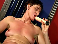 Short-haired mature woman fucks her anus with her dildo