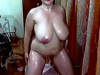 Curvy brunette milf demonstrates her oiled body for the webcam