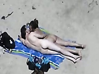 Amateur couple play with each other's genitals on a beach