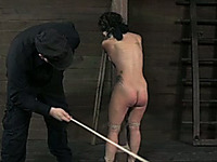 Brunette slave girl with great round ass is beaten with wooden stick