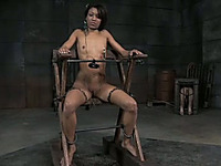 Flat chested ebony girl is bounded with iron devices and chains