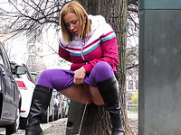 Light haired chick pulls down her purple pants and pisses outdoors