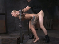 Busty tattooed blonde is fixed to the metal bar and fucked really hard