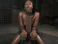 Oiled submissive black chick stands on knees while blowing black tool