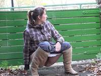 Cute brunette country girl in plaid shirt pees behind the fence