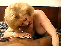 Mature and busty blonde woman on the bed giving sensual head