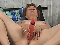 Mature redhead woman fucks herself with a huge sex toy