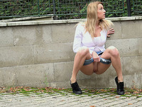 Blonde sexy teen babe hides behind the stone wall and pisses on the street