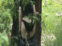 Redhead teen with pale skin ass pisses in the woods behind the tree