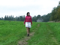Brunette Russian girl outdoors squats and pisses on the grass