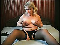 Mature plump woman with big breasts masturbating in solo on the bed