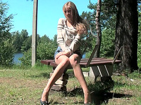 Lean and busty young blondie sits on the bench and spreads her legs