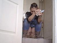 White stranger girl in blue jeans pisses in the toilet room