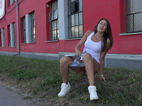 Stunning brunette teen beauty squats on the lawn and pisses