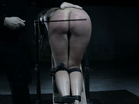 White sexy curvaceous lady shackled to the wooden bar and caned