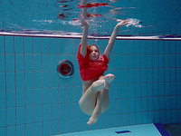Slender and cute redhead white girl dives in the pool and undresses underwater