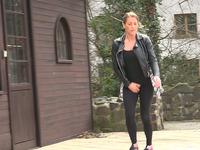 Lewd shameless brunette in black jacket pisses outdoors on the street