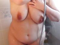 Kinky mature wife flashes her big tits while taking a shower