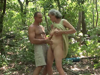 This lewd granny is sucking a muscular man's dick in the woods