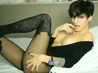 Tattooed girl with black short hair in stockings teases