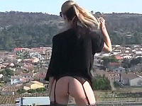Seductive blonde exhibitionist posing by the highway