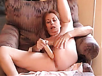My mature busty wife dildos her bushy twat in a living room
